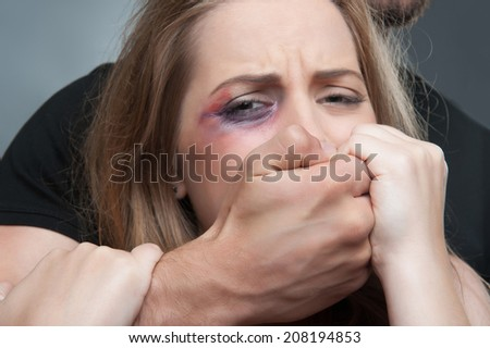 Pitiable scared young woman having black eye tearing herself away from her estranged husband standing behind her in black shirt. Isolated on grey background