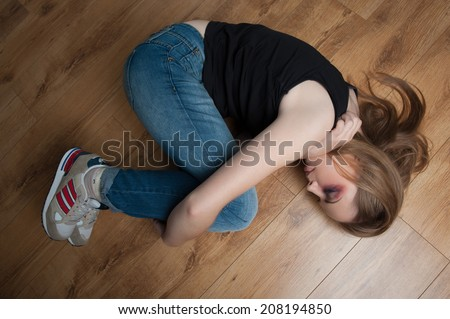 Pitiable young girl with black eye wearing black shirt and jeans grappling herself with her hands lying on the floor - stock photo