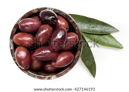 Pitted black kalamata olives in small bowl with leaves, isolated.  Top view.