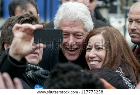 PITTSBURGH, PA - NOVEMBER 5:  Former President Bill Clinton poses with attendees of a rally while campaigning for Barack Obama in Pittsburgh, PA on November 5, 2012. - stock photo