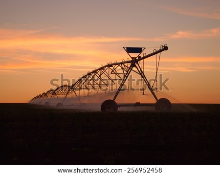 Pivot water system on a farm field at sunset, agriculture irrigation machine silhouette - stock photo
