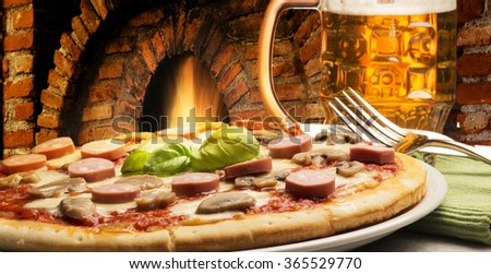 pizza and beer on the table near the owen - stock photo