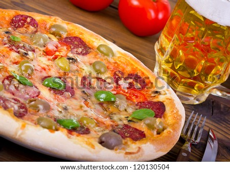 Pizza and beer on the wooden table - stock photo