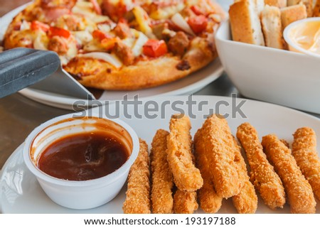 Pizza and chicken stick and bread stick on table. - stock photo