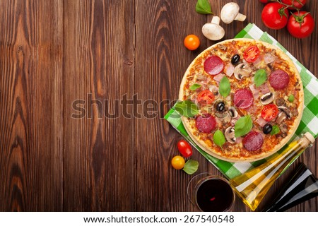 Pizza and red wine on wooden table background. Top view with copy space - stock photo