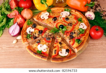 pizza and vegetables on wooden background