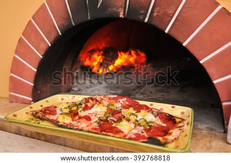 Pizza baked in brick oven on a colorful plate, narrow focus.