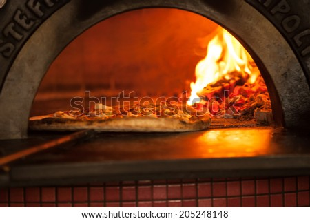 Pizza baking close up in the oven - stock photo