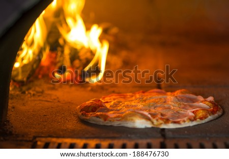 Pizza baking in traditional oven - stock photo