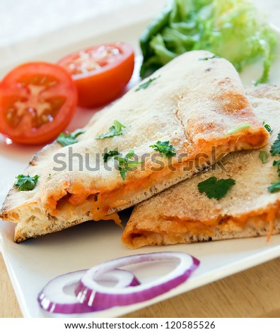 Pizza Calzone on a white plate with a salad accompaniment