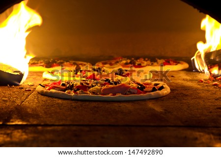 Pizza cooking in a tradition oven - stock photo