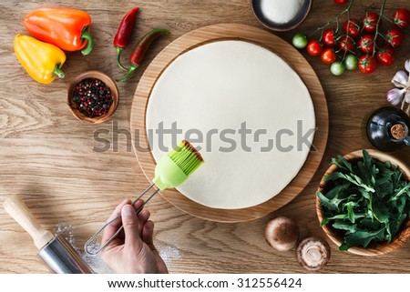 Pizza cooking process: spreading tomato sauce on pizza base with a silicone pastry brush. Wooden background, top view. - stock photo