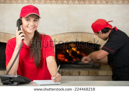 Pizza delivery service and chef puts the pizza inside the wood oven to bake. - stock photo