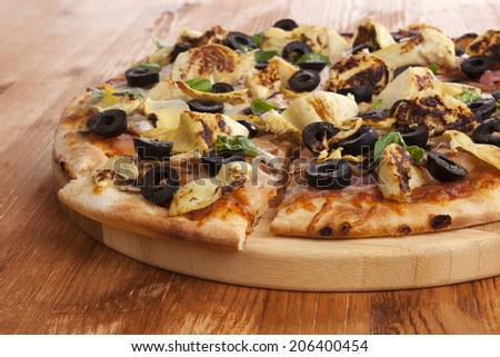 Pizza detail on wooden background. Italian cuisine, pizza with black olives, artichokes and ham. Culinary eating.  - stock photo
