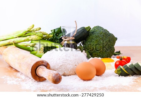 Pizza dough and ingredients flour and a rolling pin on wooden table. - stock photo