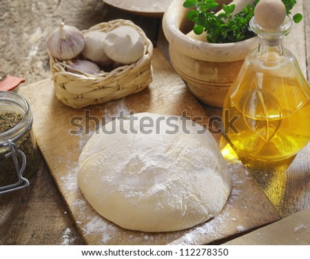Pizza dough being left to rise surrounded by fresh herbs, garlic and ingredients in the kitchen - stock photo