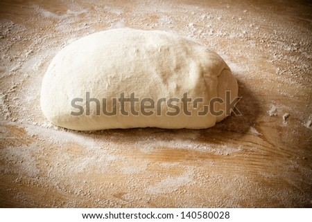 Pizza dough on wooden tabletop with flour