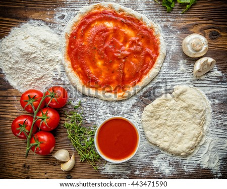 Pizza dough with ingredients and tomato sauce served on rustic wooden table. Aerial shot, copyspace for text - stock photo