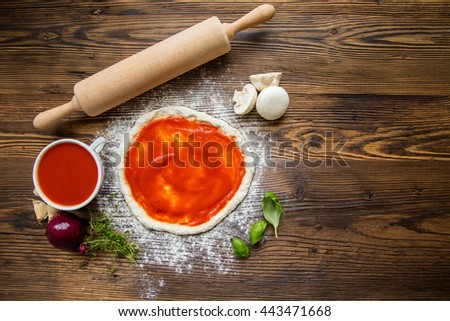 Pizza dough with ingredients, tomato sauce and wooden rolling-pin served on rustic wooden table. Aerial shot, copyspace for text - stock photo