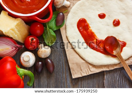 Pizza dough with tomato sauce smile and parmesan cheese, fresh tomatoes, basil, red onion, olives and mushrooms on a wooden background.