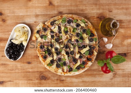 Pizza eating. Fresh pizza and fresh pizza ingredients on wooden table, top view. Italian pizza eating.  - stock photo