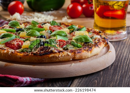 Pizza hawaii with beer served on cutting board