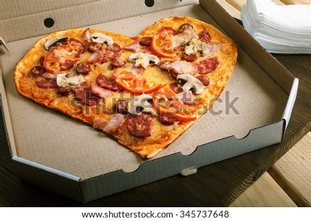 Pizza heart shape on dark wooden background top view. Thin pastry crust on wooden desk - stock photo