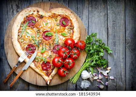 Pizza heart shape with cheese and tomato on vintage boards - stock photo