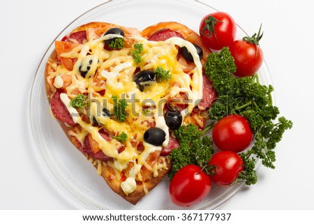 Pizza heart with olives, salami, cheese and tomatoes