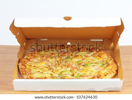 Pizza in box on wood - stock photo