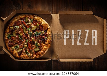 pizza in the in delivery box with pizza text on the wood - stock photo