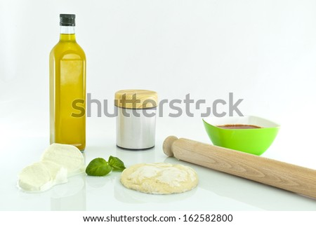 Pizza ingredients and rolling pin on white background