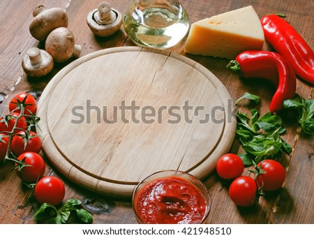 Pizza ingredients and tray on wooden board - stock photo