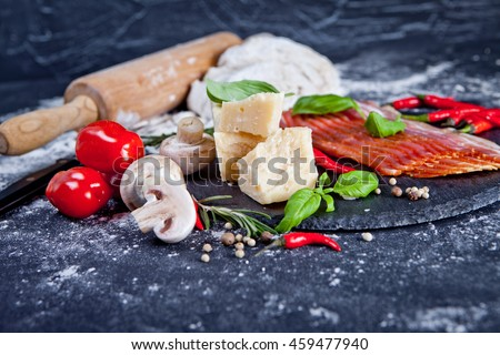 Pizza ingredients - dough, chili pepper, cheese, mushrooms, prosciutto and tomato