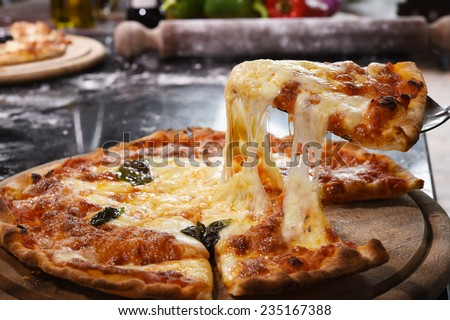 Pizza lifting slice on wooden board. - stock photo