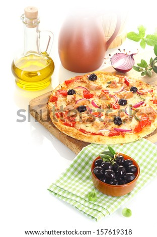 Pizza made of tuna, olives, onion and basil over a wooden board surrounded by the composing ingredients - stock photo