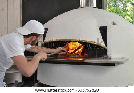 Pizza man portrait.baker man cooking pizza on traditional wooden oven.Pizza oven - stock photo