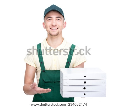Pizza man. Smiling young delivery man is holding a pizza boxes while isolated on white. - stock photo