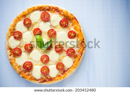 Pizza Margherita on blue background top view - stock photo