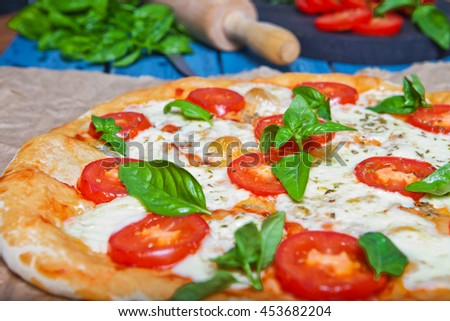 Pizza Margherita on dark wooden background