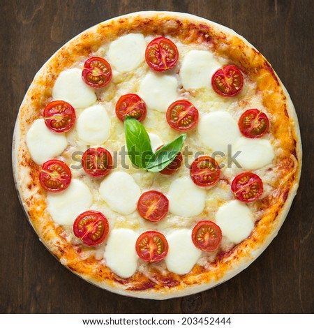 Pizza Margherita on dark wooden background top view - stock photo