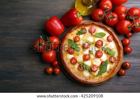 Pizza Margherita with arugula, red pepper, tomatoes on wooden table - stock photo