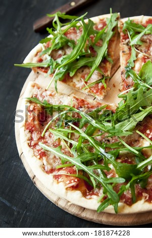 Pizza Margherita with Fresh Arugula Leaves on Wooden Board - stock photo