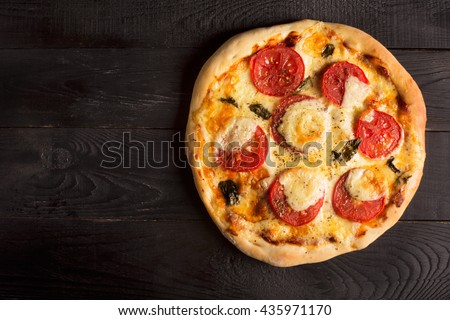 Pizza Margherita with tomatoes and mozzarella cheese on a black table