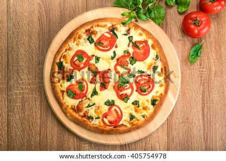 Pizza Margherita with tomatoes, mozzarella and basil on a wooden board, flat lay, top view - stock photo