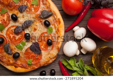 Pizza margherita with tomatoes, olives and basil on vintage rustic background  - stock photo