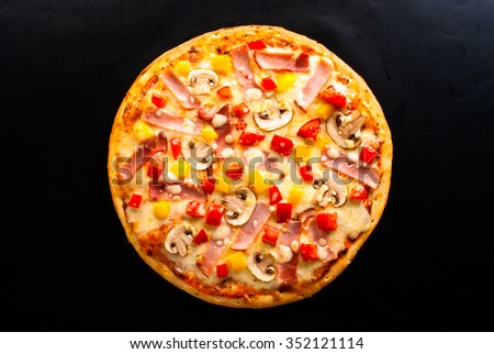 pizza on a dark background with ham, mushrooms, cheese and sweet pepper top view - stock photo