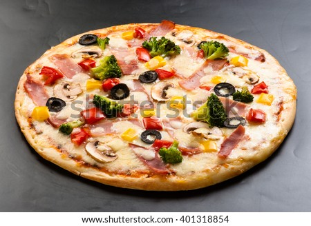 pizza on a dark background with ham, mushrooms, cheese, cauliflower, olives and sweet pepper top view - stock photo