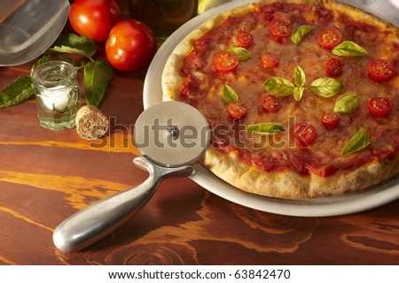 Pizza on a wooden table with ingredients