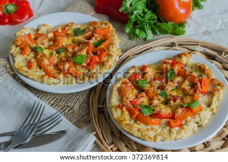 Pizza on the basis of chicken with tomatoes, peppers and cheese